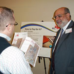 study team member talks about potential financing options with open house attendee